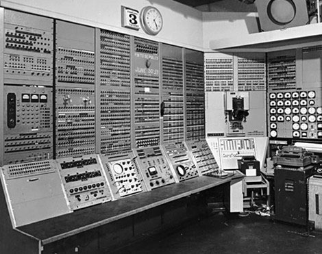 Early computer that takes up an entire room and looks very complex to operate